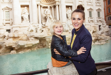 Portrait of happy modern mother and daughter tourists against Trevi Fountain Stock Photo