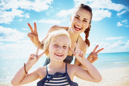 Happy modern mother and child in beachwear on the beach showing victory gesture