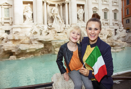 Happy young mother and child travellers with Italian flag Stock Photo