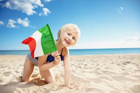 Portrait of happy girl in swimwear with Italian flag on the seacoast
