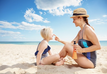 Smiling modern mother and child in swimsuit on the beach applying suntan lotion