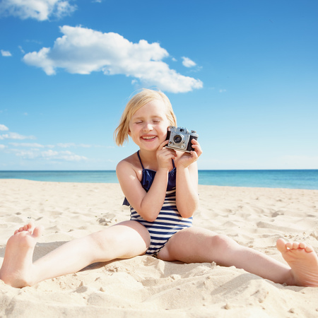 Smiling girl in beachwear with retro film photo camera on the beach