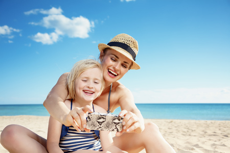 Happy young mother and daughter in swimwear taking selfie with smartphone on the beach
