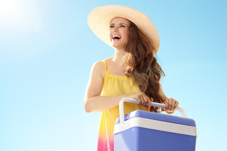 Happy healthy woman in colourful dress with plastic cooler box looking at copy space against blue sky