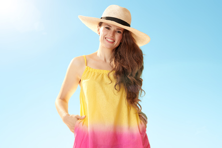 Portrait of smiling fit woman in straw hat against blue sky