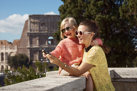 Happy young mother and daughter travellers not far from Colosseum viewing photos on camera