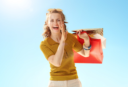 Happy trendy woman with shopping telling exciting news against blue sky