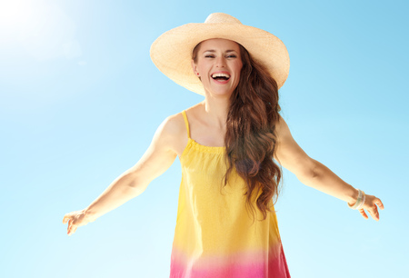 Portrait of cheerful active woman in straw hat against blue sky