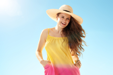 Portrait of happy healthy woman in colourful dress against blue sky