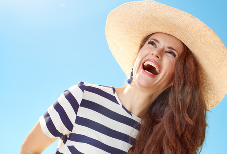 Cheerful modern woman in straw hat looking into the distance against blue sky