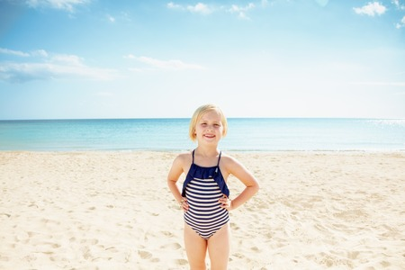 Portrait of happy child in swimsuit standing on the seashore