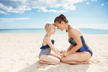 Happy modern mother and daughter in swimwear on the seacoast