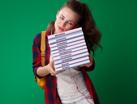 modern student woman in a red shirt with backpack and headphones sleeping on a pile of books against green background