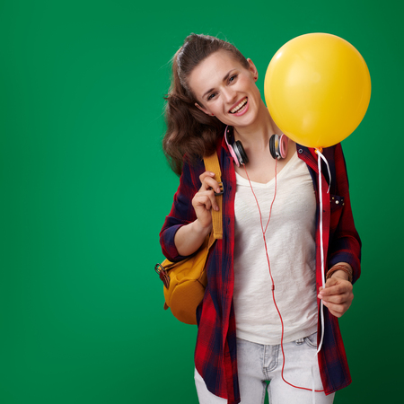 smiling modern student woman in a red shirt with backpack and headphones with a yellow balloon on green background Stock Photo
