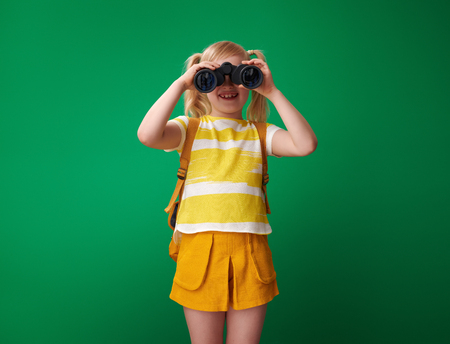 smiling school girl with backpack looking through binoculars isolated on green background