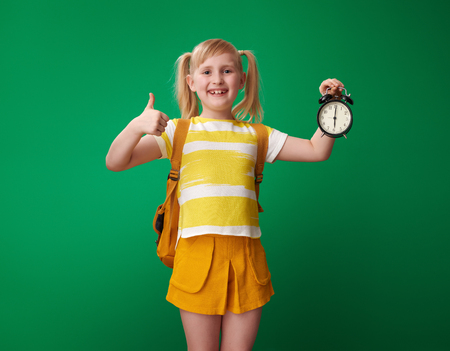 happy school girl with backpack with alarm clock showing thumbs up isolated on green background Stockfoto