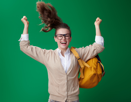 smiling modern student woman jumping and rejoicing isolated on green background