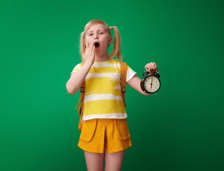 tired pupil with backpack with alarm clock and yawing isolated on green Stockfoto