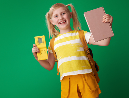 happy school girl with backpack chosen book instead of video game on green background