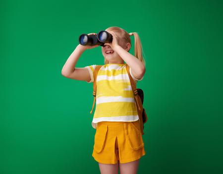 smiling pupil with backpack looking into the distance through binoculars isolated on green 版權商用圖片