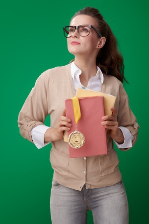 proud modern student woman with books and medal looking at copy space on green background 스톡 콘텐츠