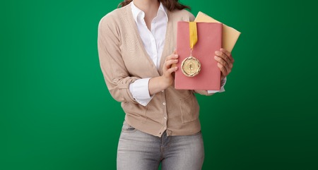 happy modern student woman with books and medal on green background