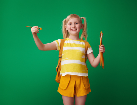 smiling school girl with backpack holding drawing brushes on green background Banque d'images - 107450362