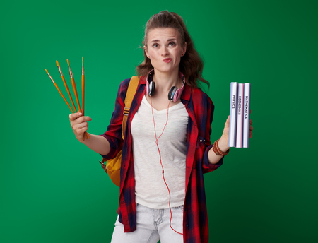 pensive modern student woman in a red shirt with backpack and headphones choosing between sciences and art isolated on green background Stock Photo