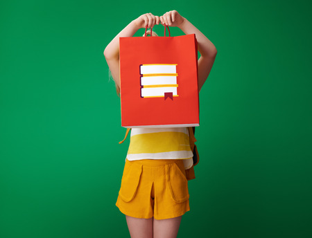 school girl with backpack holding shopping bag with stationery in the front of face on green background