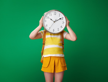 pupil with backpack holding clock in the front of face against green background Stock Photo