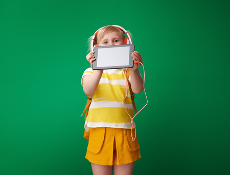 pupil with backpack showing tablet PC blank screen isolated on green