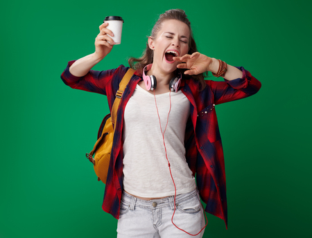 young student woman in a red shirt with backpack and headphones with coffee cup yawing isolated on green Stock Photo