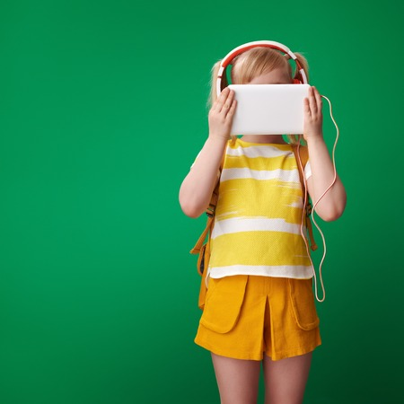school girl with backpack with tablet PC listening to the music with headphones isolated on green background