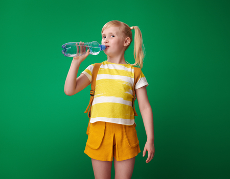 happy pupil with backpack drinking water isolated on green Stock Photo
