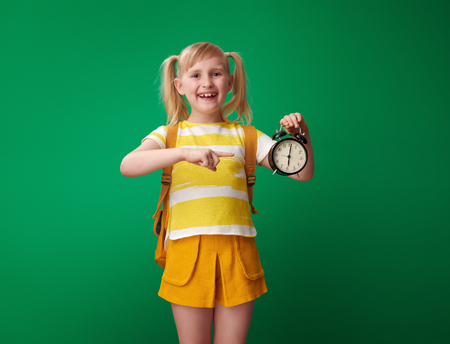 smiling pupil with backpack pointing at alarm clock isolated on green background Stockfoto