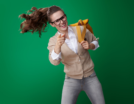 happy young student woman jumping and pointing in camera isolated on green