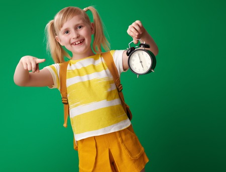 happy pupil with backpack pointing at alarm clock on green background