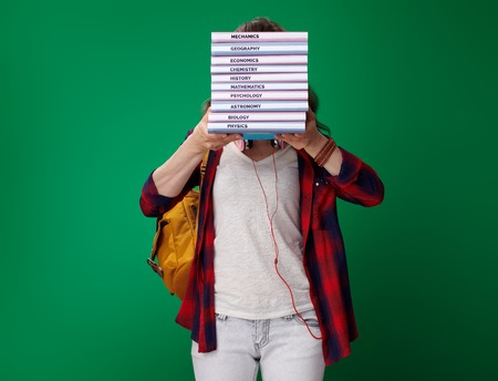young student woman in a red shirt with backpack and headphones holding a pile of books in the front of face isolated on green background Stock Photo