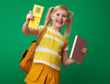 happy pupil with backpack chosen video game instead of book against green background