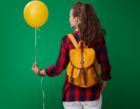 Seen from behind modern student woman in a red shirt with backpack and headphones with a yellow balloon isolated on green