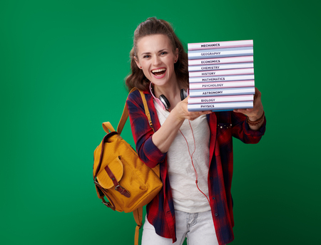 happy modern student woman in a red shirt with backpack and headphones giving a pile of books against green background Stockfoto