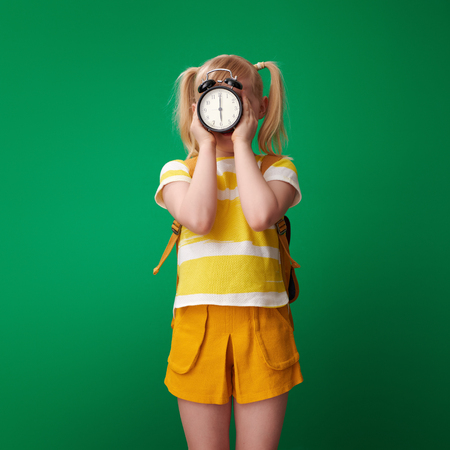 school girl with backpack holding alarm clock in the front of face against green background Stockfoto