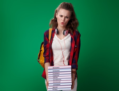 tired modern student woman in a red shirt with backpack and headphones with pile of books on green background