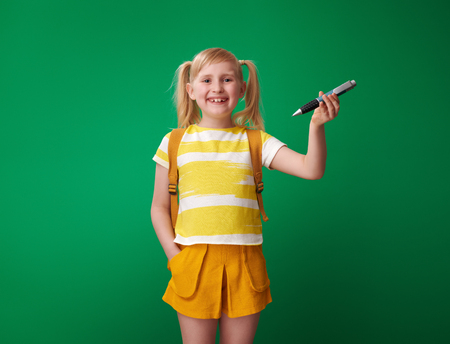 happy pupil with backpack showing big pen isolated on green background Фото со стока