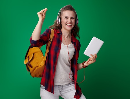 smiling modern student woman in a red shirt with backpack and headphones and tablet PC with fingers snapping isolated on green