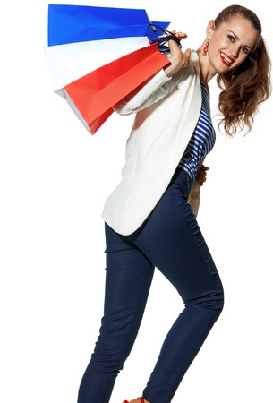 Luxury Shopping. The French way. happy young fashion-monger in white jacket isolated on white background with shopping bags painted in the color of the French flag Stock Photo