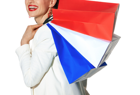 Luxury Shopping. The French way. smiling modern woman in white jacket isolated on white background with shopping bags painted in the color of the French flag Stock Photo