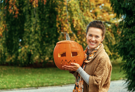 Trick or Treat. smiling modern woman on Halloween outdoors showing pumpkin Jack O'Lantern Stock Photo