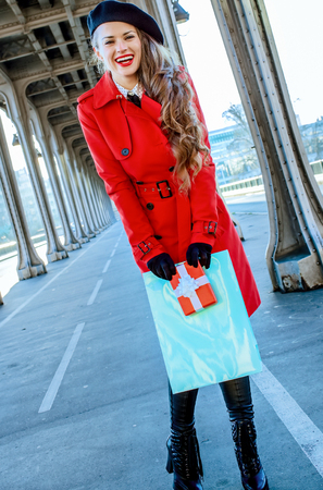 Bright in Paris. smiling modern woman in red trench coat on Pont de Bir-Hakeim bridge in Paris with shopping bag and Christmas present box 스톡 콘텐츠