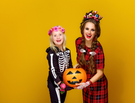 Colorful halloween. happy modern mother and child in Mexican style halloween costume on yellow background holding jack-o-lantern pumpkin